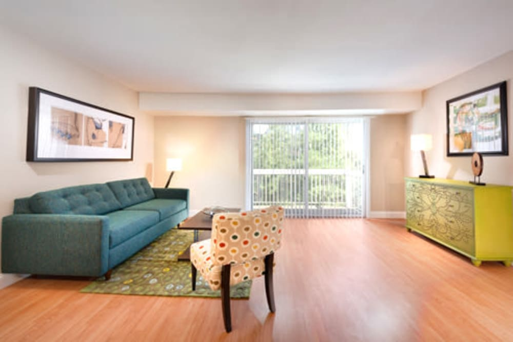 A living room with wood-style flooring at The Landings I & II Apartments in Alexandria, Virginia
