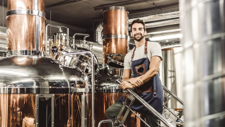 Man standing in front of polished copper and chrome distilling equipment, facing the camera and smiling.