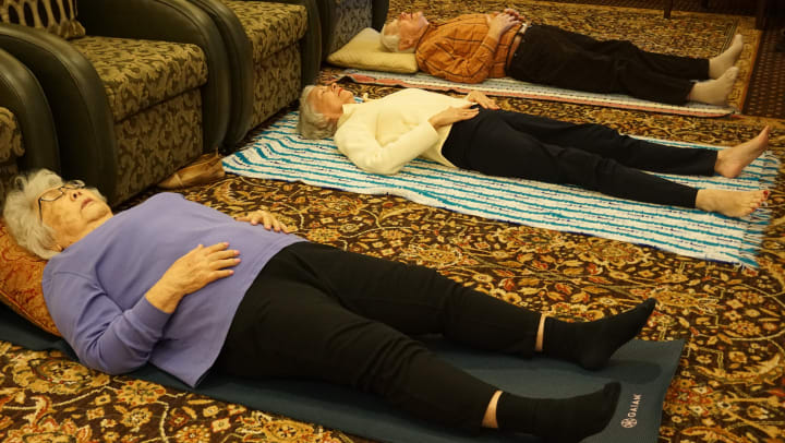 Three seniors lying on separate yoga mats are modeling the belly rise and fall yoga pose.