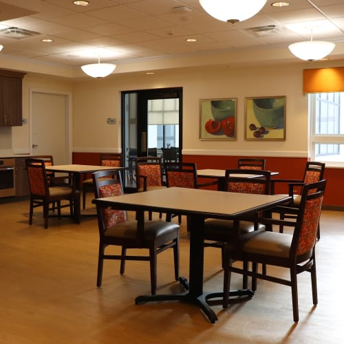 Causal resident dining hall with tables and kitchen amenities at First & Main of Bloomfield Township in Bloomfield Township, Michigan
