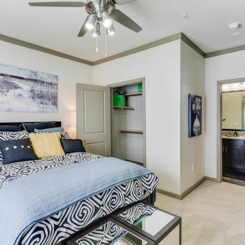 Master bedroom with a ceiling fan and en suite bathroom in a model home at Tacara at Westover Hills in San Antonio, Texas