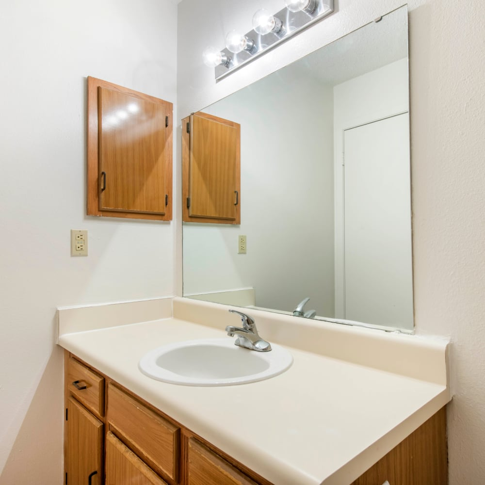 Bathroom with a large vanity mirror at Compass in Melbourne, Florida