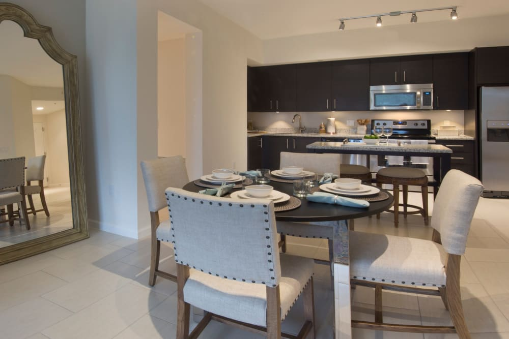 Beautiful dining room with table and chairs and view of kitchen at Doral View Apartments in Miami, Florida