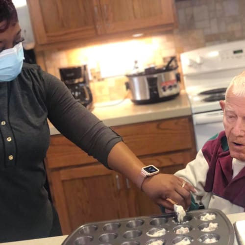 Masked caretaker cooking with a resident at Oxford Glen Memory Care at Sachse in Sachse, Texas