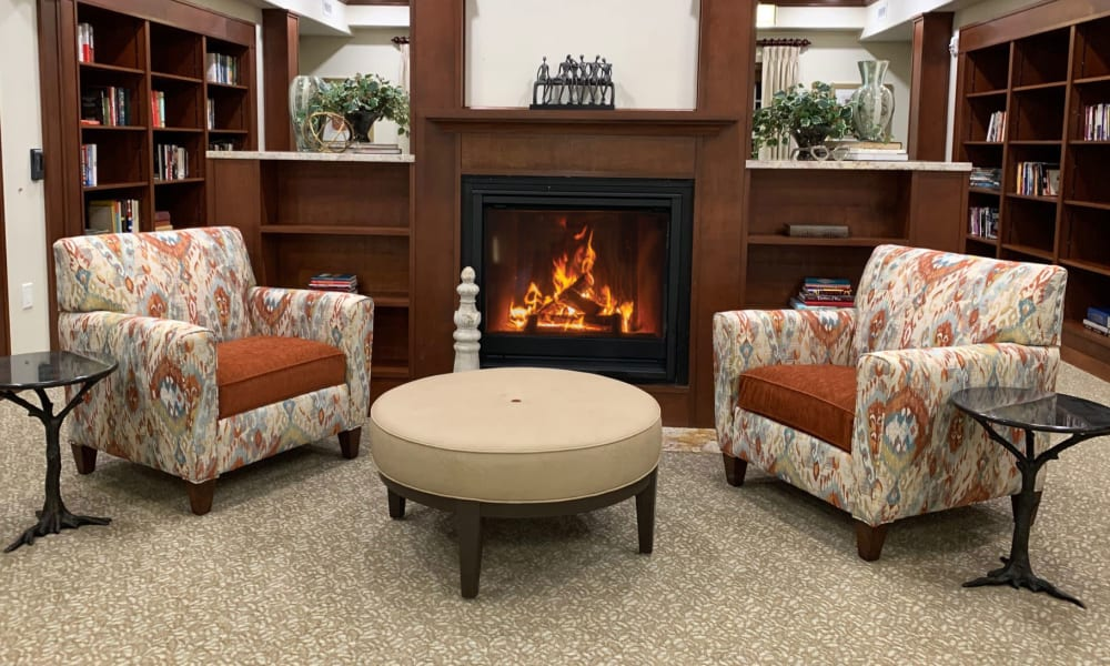Fireside seating in the library at The Savoy Gracious Retirement Living in Winter Springs, Florida