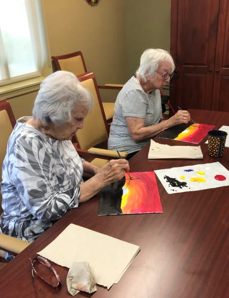 A pair of Oaks residents work on their desert sunset paintings.