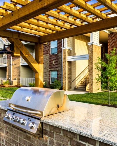 Gas BBQ grill with spacious stone countertop underneath pergola at Valley Farms in Louisville, Kentucky