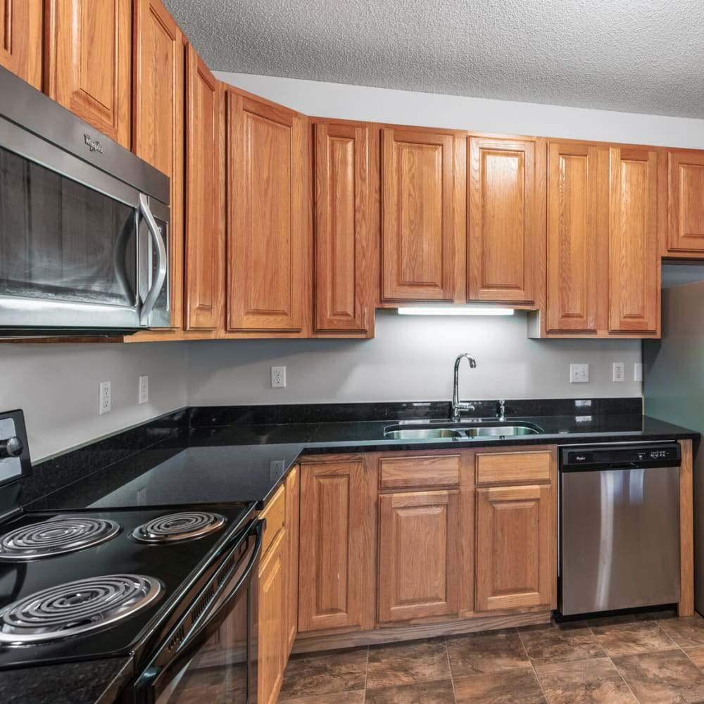 Wood cabinetry and hardwood flooring in a model townhome's kitchen at Oaks Lincoln Apartments & Townhomes in Edina, Minnesota