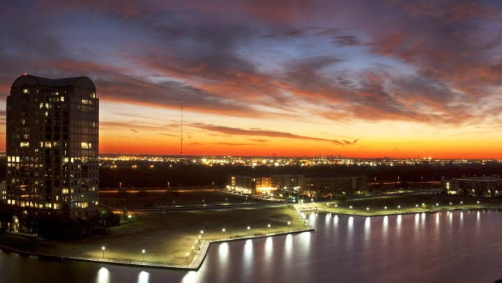 A landscape view of water, green space, buildings, and city lights in the distance, with a colorful sunset in the sky.