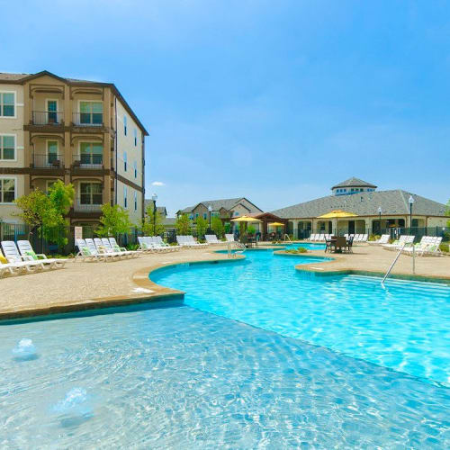 Winding resort-style swimming pool with a sun deck at Olympus Woodbridge in Sachse, Texas