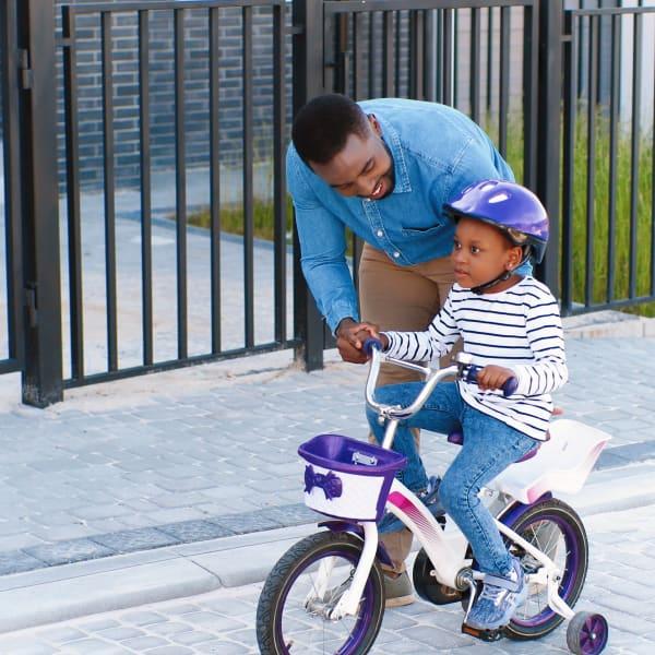 Father teaching his child to ride a bike near Ocio Plaza Del Rio in Peoria, Arizona