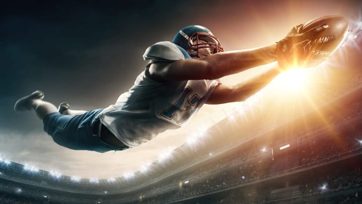 An American football player diving with a football.