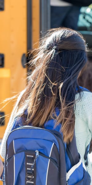Resident's child getting on the school bus near Hidden Hills Condominium Rentals in Laguna Niguel, California