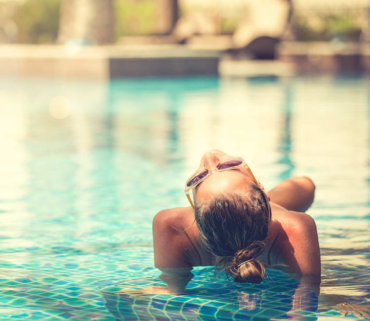 Resident relaxing on the in-pool sun deck at Canyon View in Las Vegas, Nevada