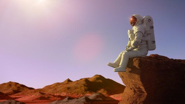 Astronaut on planet Mars sitting on a ledge