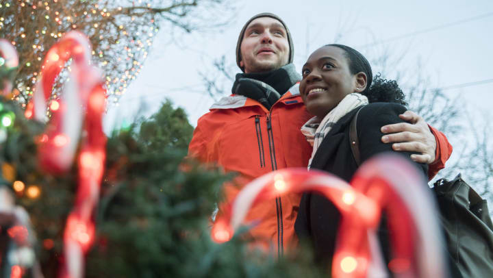 Young couple looking around a Christmas tree lot