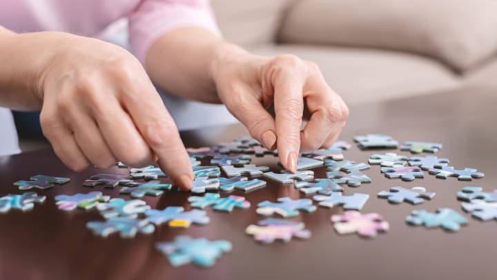 Closeup of a senior woman's hands solving a jigsaw puzzle on a table.