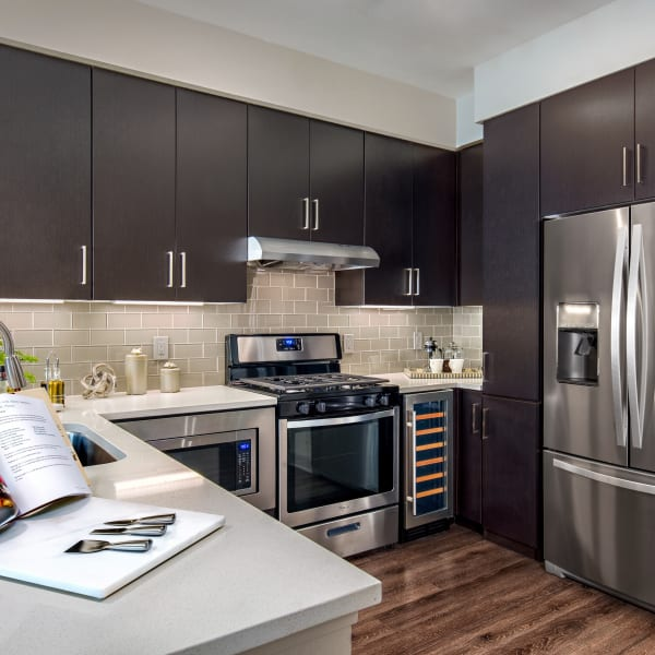 Gourmet kitchen with dark wood cabinetry and stainless-steel appliances in a model home at The Core Scottsdale in Scottsdale, Arizona