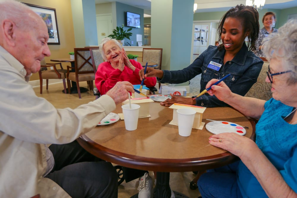 A caretaker assisting a residents with a painting activity at Harmony at Spring Hill in Lorton, Virginia