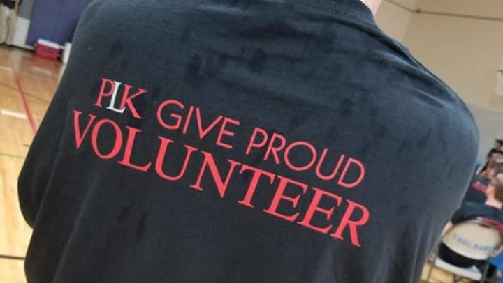 PLK give proud volunteer wearing PLK give proud shirt