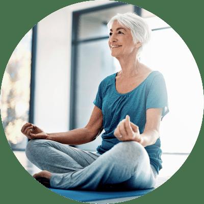 Resident sitting cross-legged doing yoga at Hanover Place in Tinley Park, Illinois