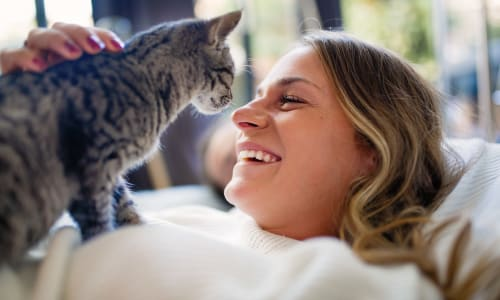 Resident and her happy cat in their pet-friendly home at Ballena Village Apartment Homes in Alameda, California