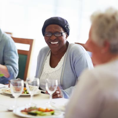 Residents laughing and smiling over a meal at Arbor Glen Senior Living in Lake Elmo, Minnesota
