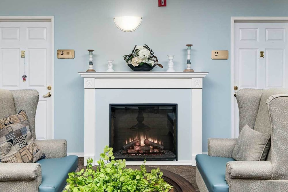 Fireplace seating in a calming blue room with comfy arm chairs at The Springs at Grand Park in Billings, Montana