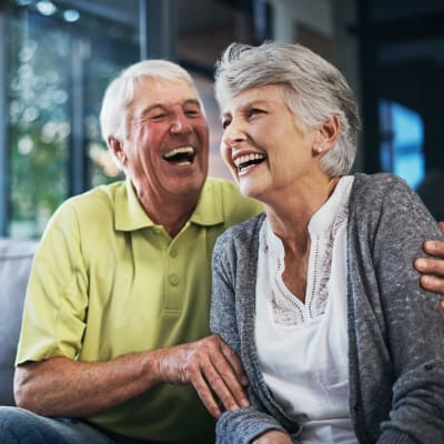 Resident couple sitting on the couch laughing at York Gardens in Edina, Minnesota