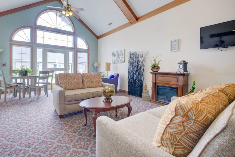 Welcoming airy and sunny sitting room with comfy couches and fireplace at Brookstone Estates of Vandalia in Vandalia, Illinois
