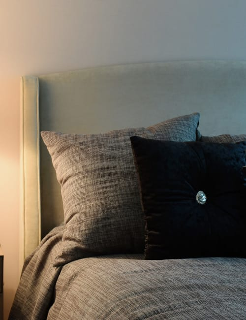 Comfortable bed at Calloway Row Apartments in Baltimore, MD