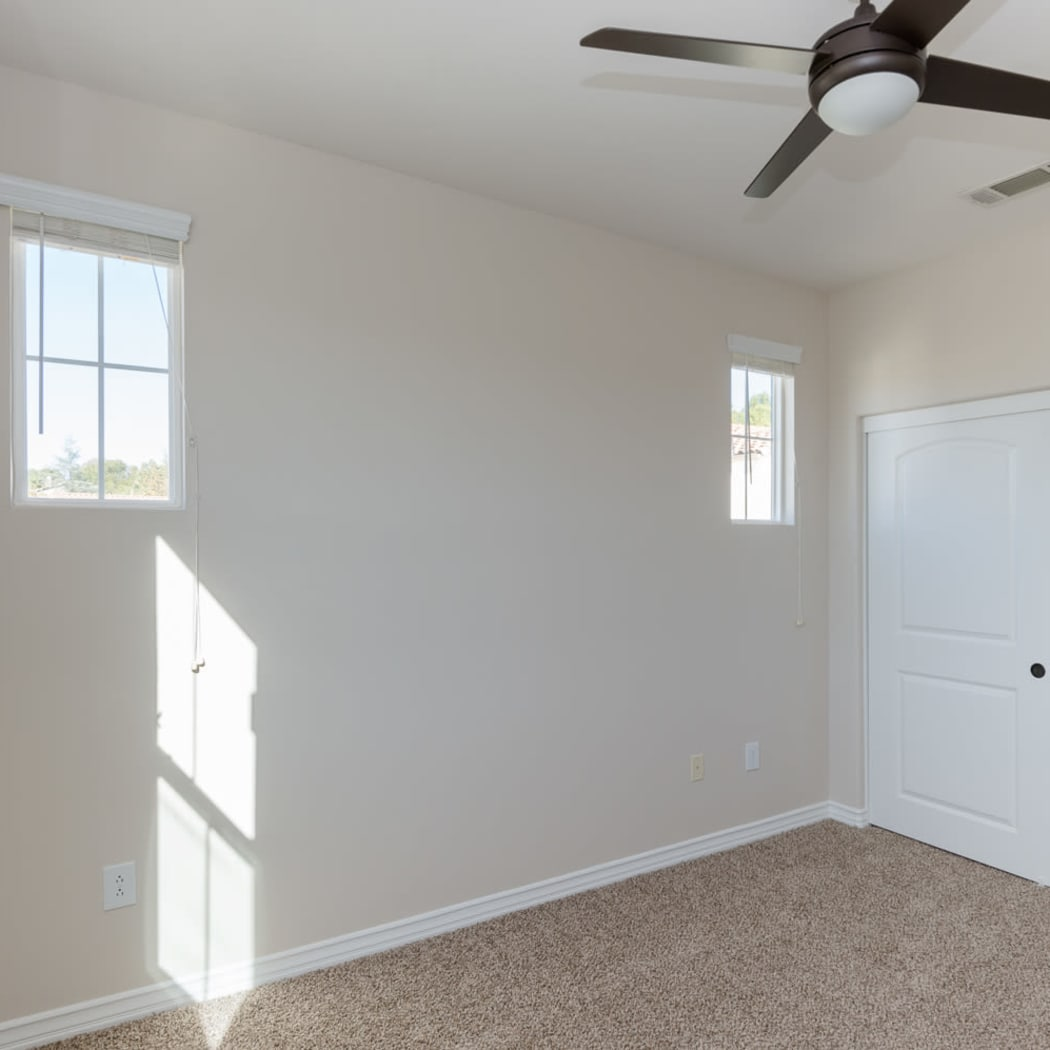 Bedroom with plush carpet and ceiling fan in model home at IMT Rancho Serrano Townhomes in Thousand Oaks, CA