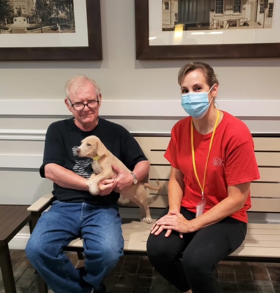 Man holds puppy in his arms sitting next to woman on a bench