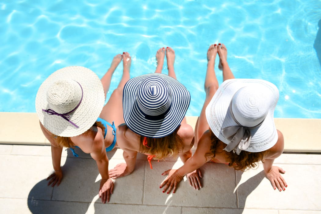 Girlfriends sunbathing by the pool at Portico at Friars Creek Apartments in Temple, Texas