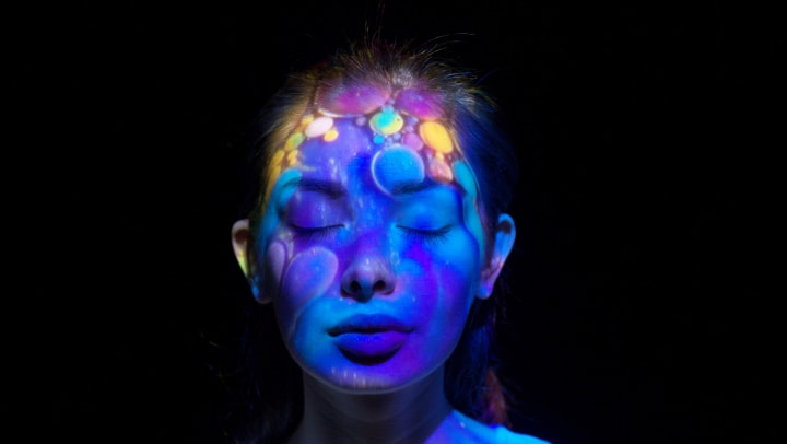 Woman with eyes closed and multiple colors projected onto her face. Set against a black background.