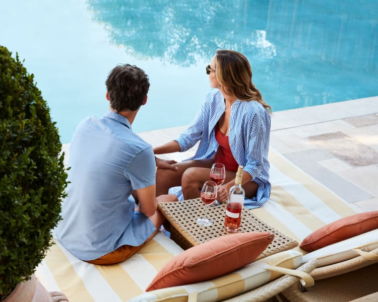 Resident couple enjoying a glass of wine near the pool at Vue Issaquah in Issaquah, Washington