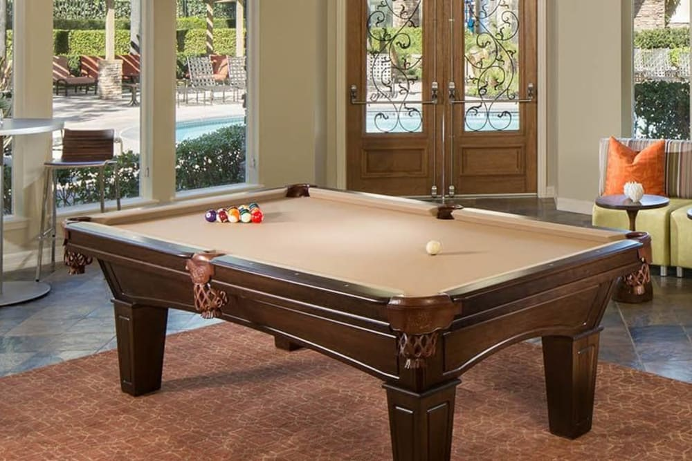 Interior view of the resident clubhouse with a billiards table at Alize at Aliso Viejo Apartment Homes in Aliso Viejo, California