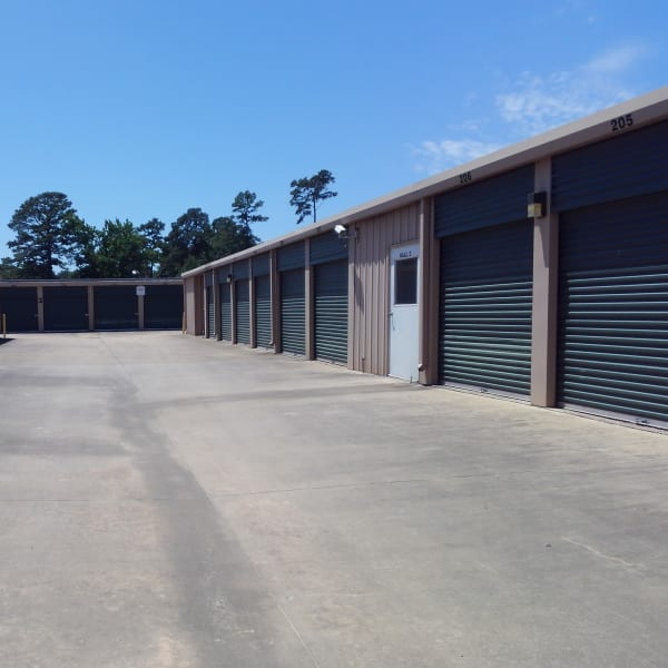 Outdoor storage units with green doors at StorQuest Self Storage in Spring, Texas