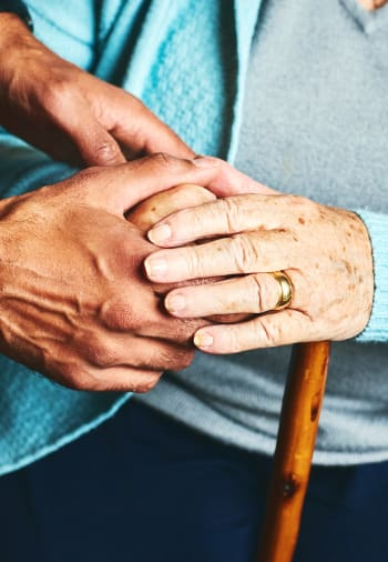 A resident and staff member holding hands at The Blake at The Grove in Baton Rouge, Louisiana.