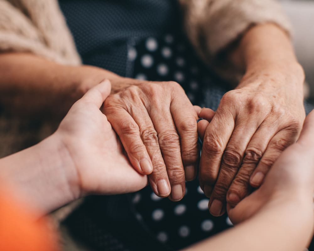 Residents holding hands in a support group at Milestone Senior Living Eagle River in Eagle River, Wisconsin.