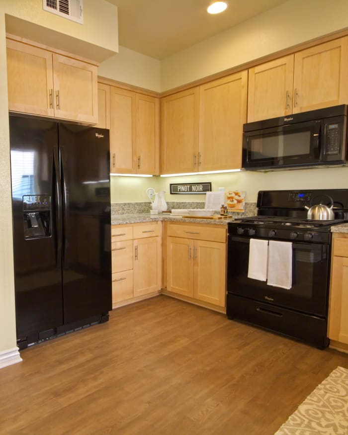Modern kitchen with hardwood floors and black appliances in model home at IMT Townhomes at Magnolia Woods in Sherman Oaks, CA