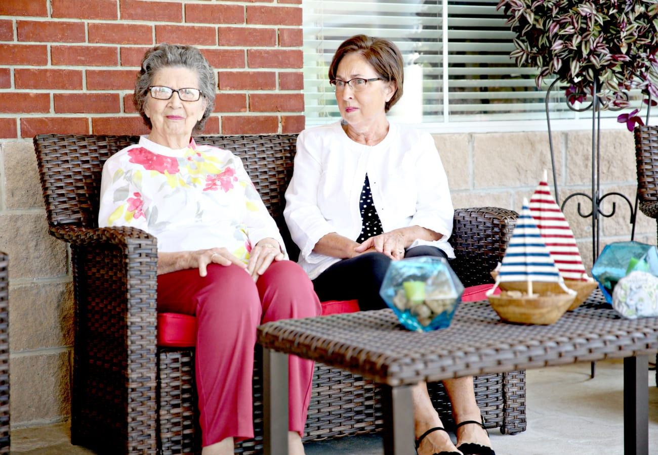 Two women sitting on an outside patio in outdoor furniture at Providence Assisted Living in Clarksville, Arkansas