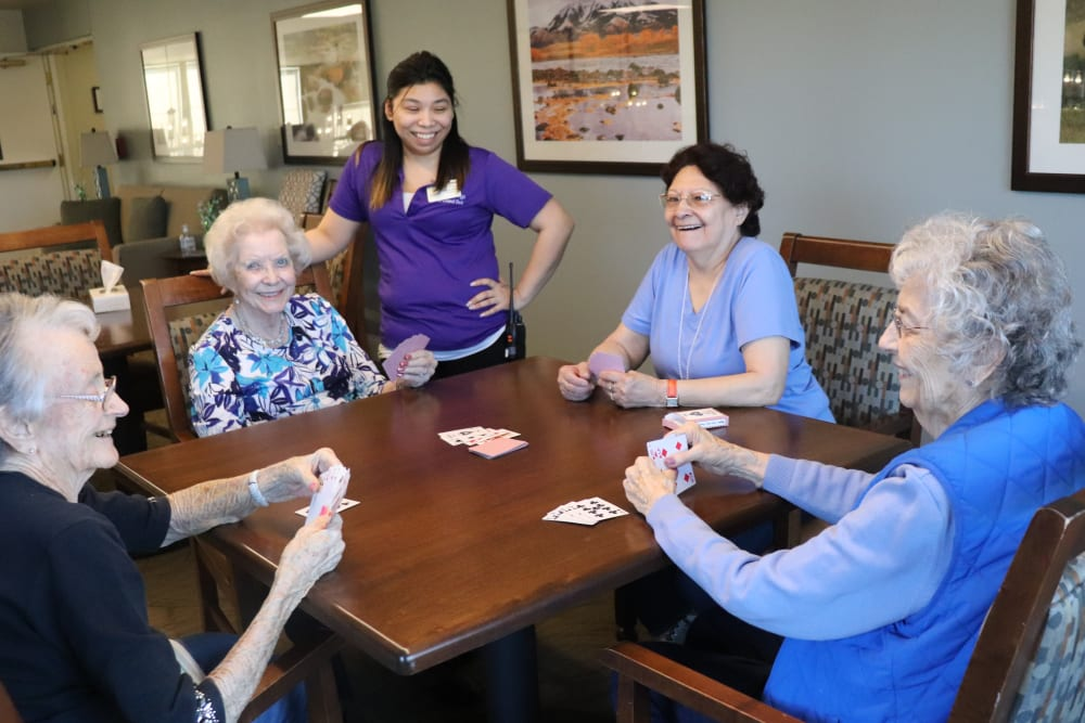 Four friends playing cards with a caregiver looking on and smiling at The Springs at Grand Park in Billings, Montana