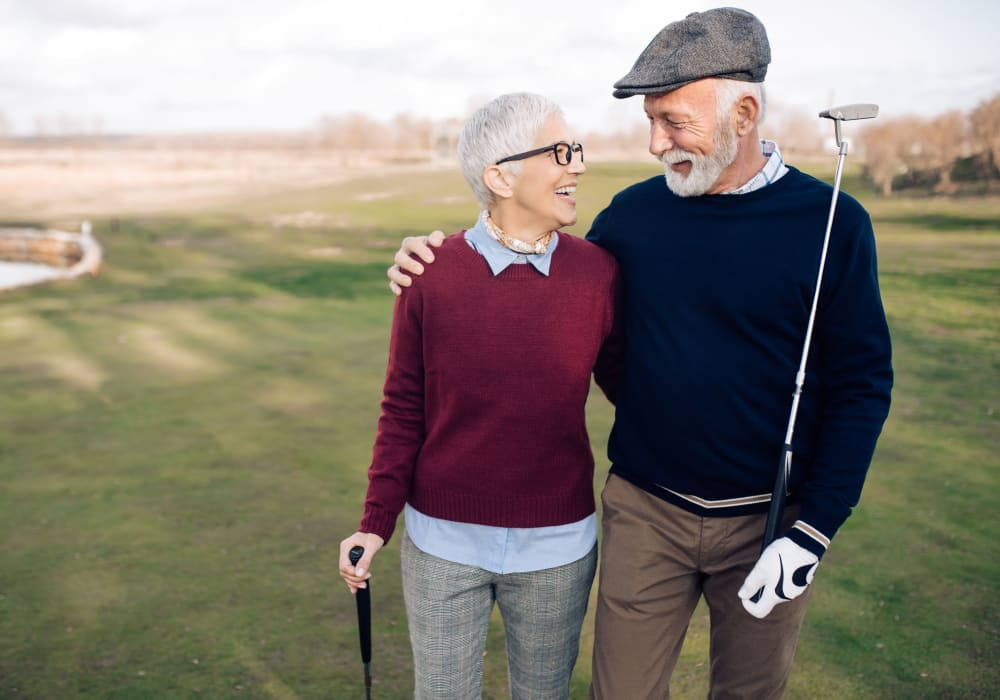 Couple playing golf at a local course near Castle Vista Senior Duplex Community in Atwater, California