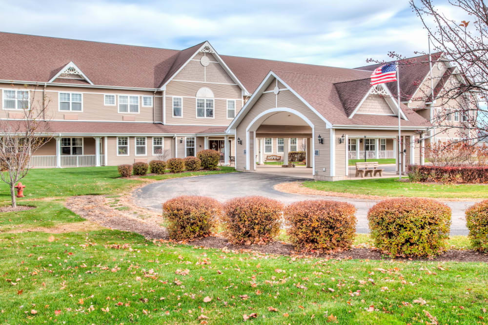 Front entrance to upscale senior living facility with grassy expanse at Grand Victorian of Sycamore in Sycamore, Illinois