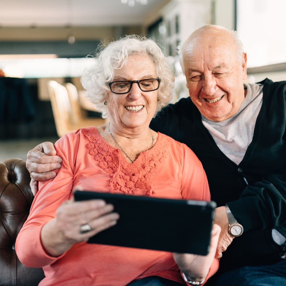 Two residents using their IPad in their senior living apartment at The Springs at Bozeman in Bozeman, Montana