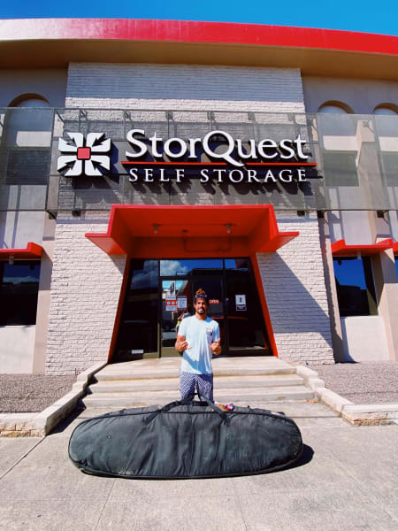 Dr. Cliff Kapono standing in front of a StorQuest Self Storage facility, with a large bag of gear in front of him