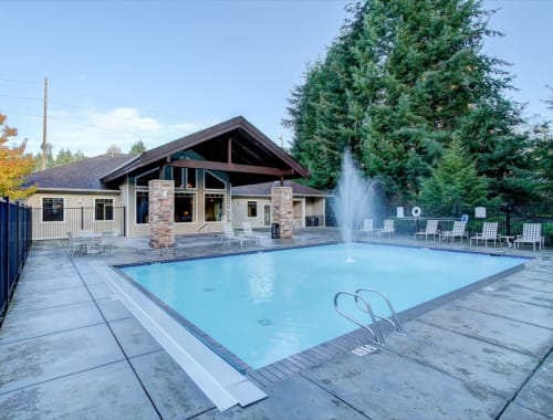 Spacious swimming pool with a water fountain at The Dakota Apartments in Lacey, Washington