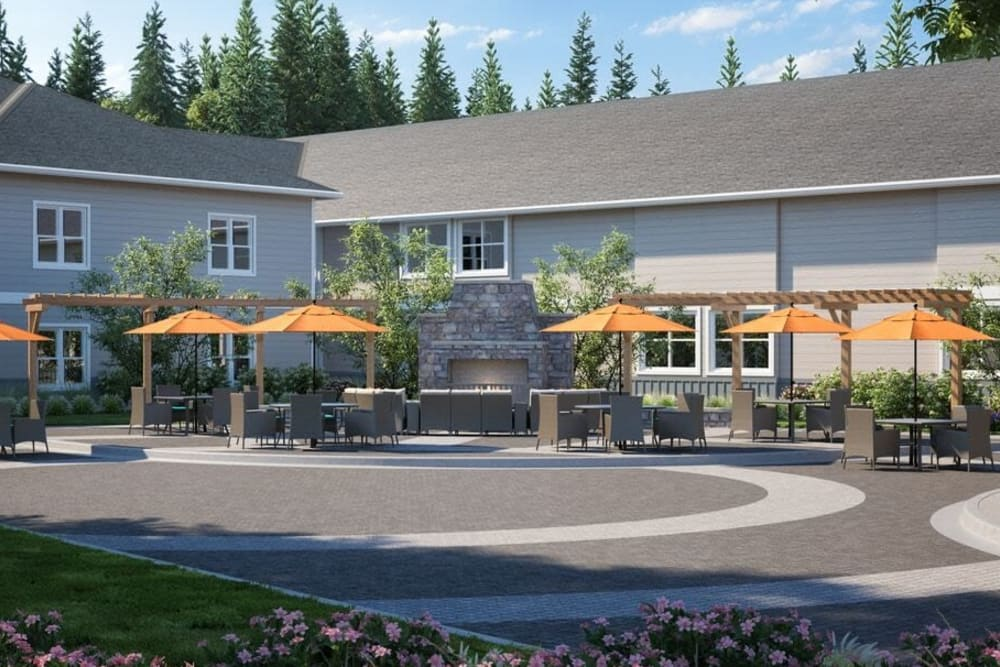 Patio area of upscale senior living facility with cheerful orange umbrellas on a sunny day at The Springs at Sherwood in Sherwood, Oregon