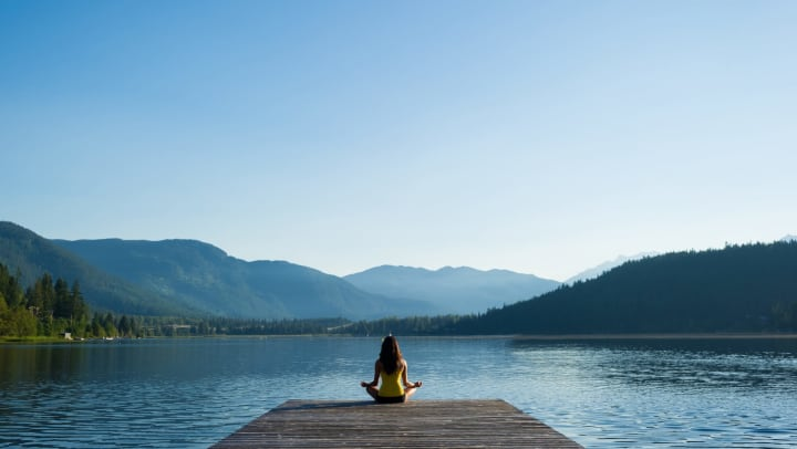 Woman sits on a dock at the edge of a lake.